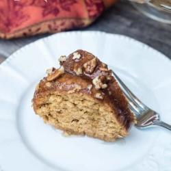 A piece of sweet potato bourbon bundt cake on a white plate with a fork.