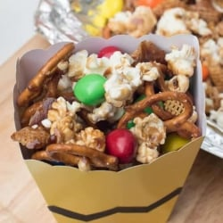 A yellow popcorn box filled with popcorn, pretzels, and M&M's.