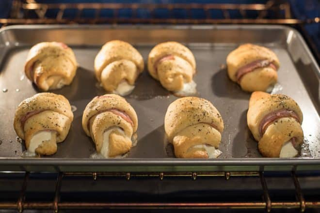 The stuffed crescents baking in the oven on a baking sheet.