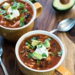 Mugs of chicken tortilla soup topped with sour cream, cilantro, and avocado.