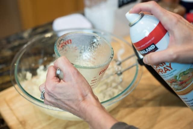 Spraying a glass measuring cup with non stick cooking spray.