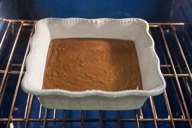 The gingerbread batter in a baking dish in the oven.