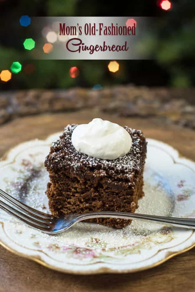 A slice of Old Fashioned Gingerbread on a pretty china plate topped with whipped cream.