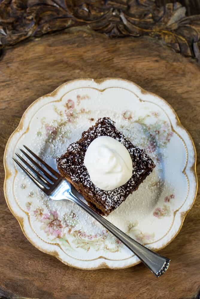 A slice of Old Fashioned Gingerbread on a pretty china plate topped with powdered sugar and whipped cream.