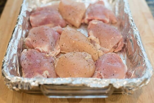 Raw chicken thighs in a foil-lined baking dish.