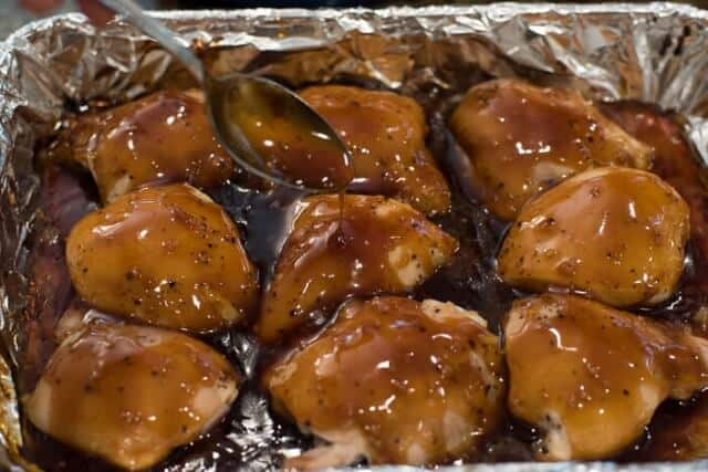 A spoon drizzling teriyaki sauce over chicken in the baking dish.