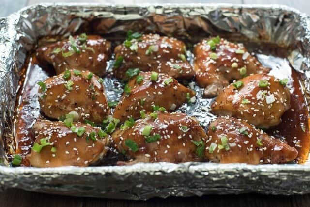 Baked Chicken Teriyaki in a foil-lined baking dish garnished with green onion and sesame seeds.