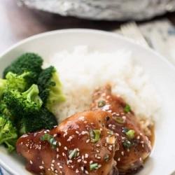 A bowl with rice, teriyaki chicken, and broccoli.