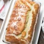 A loaf of lemon yogurt poppy seed bread topped with glaze.