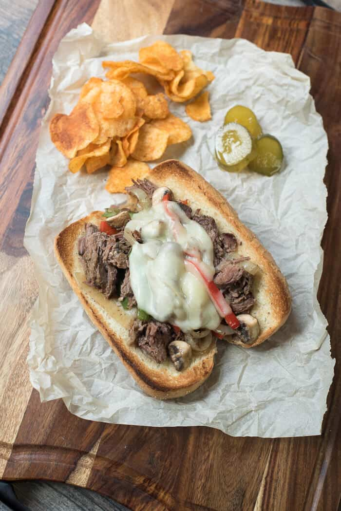 Tender shredded beef with sauteed veggies loaded on hoagie rolls with melted provolone. Slow Cooker Drip Beef Sandwiches - a super easy, crave-worthy meal!