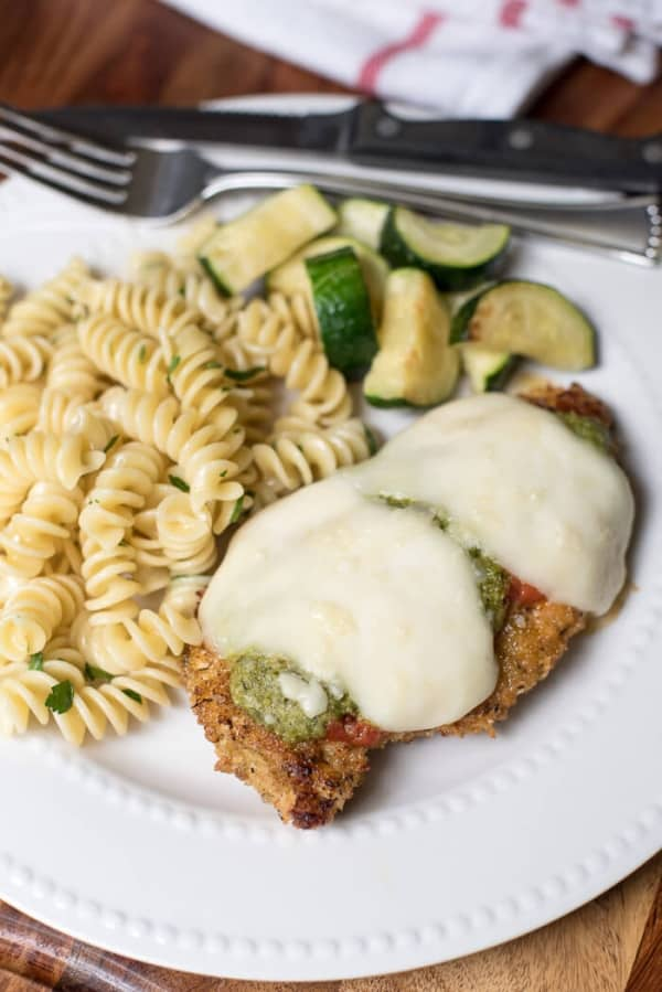 A serving of Baked Chicken Pesto Parmesan with pasta and zucchini on a white plate.