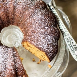 A bundt caked dusted with powdered sugar with one piece missing.