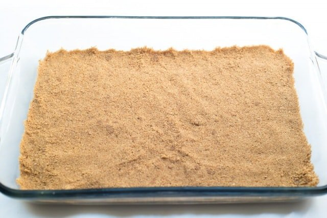 A graham cracker crust in a baking dish.