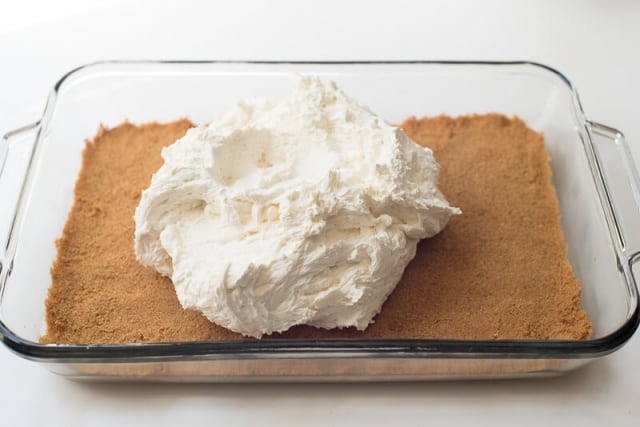 A cream cheese mixture on top of a graham cracker crust.