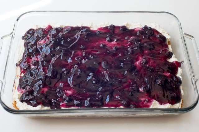 Blueberry pie filling spread out over a cream cheese layer.