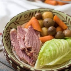 A bowl filled with sliced corned beef, cabbage, carrots, and potatoes.