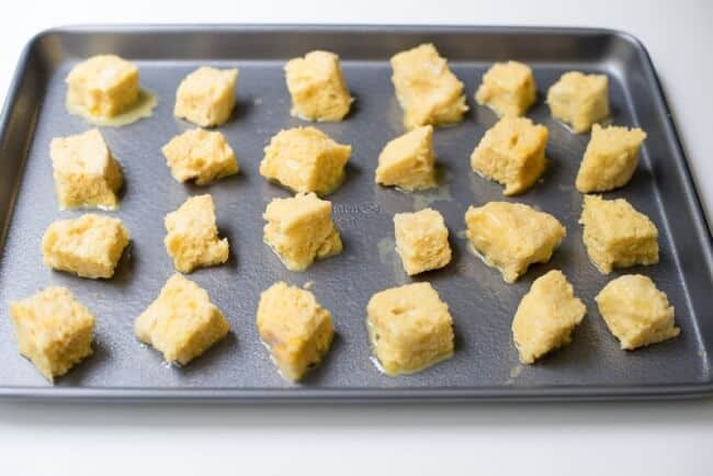 The egg soaked bread cubes on a baking sheet.
