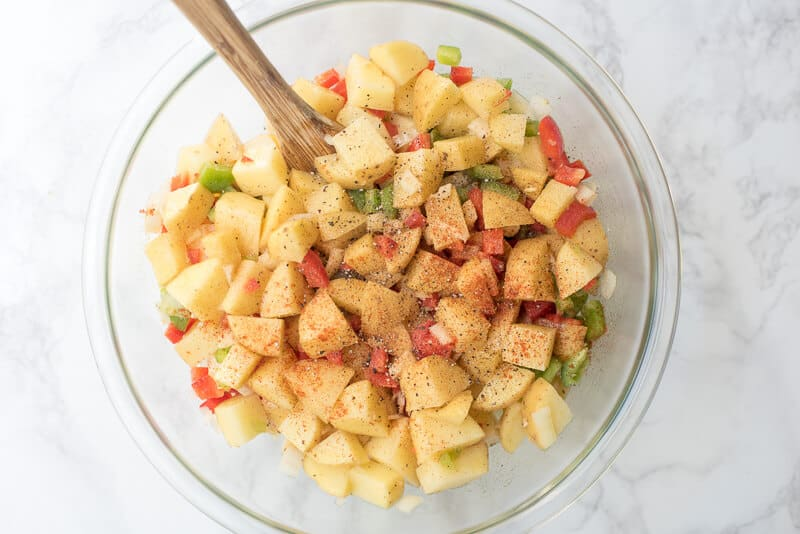 Potatoes, bell peppers, and onion with seasoning in a mixing bowl.