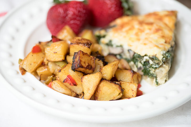 A serving of Oven Roasted Breakfast Potatoes on a white plate with quiche and strawberries