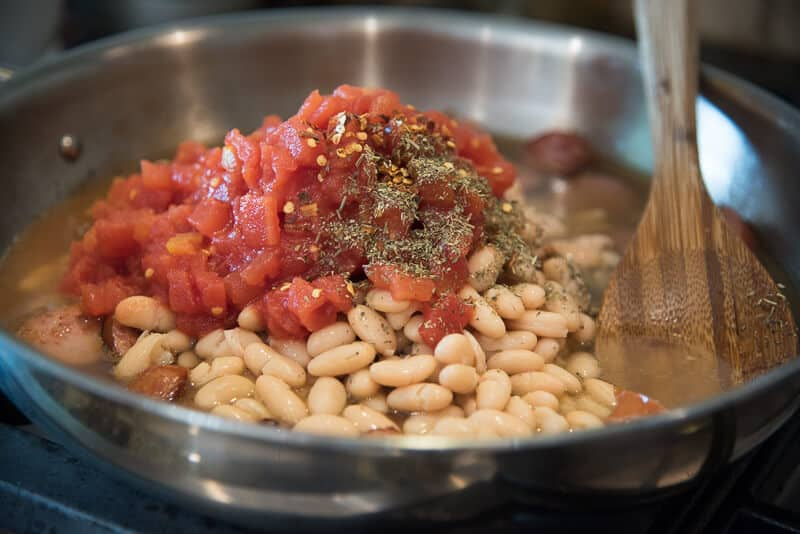 Diced tomatoes, broth, beans, and seasoning are added to the skillet.