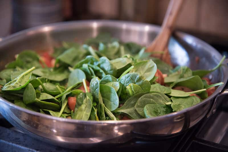 Baby spinach is added to the skillet.