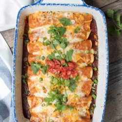 A baking dish full of enchiladas topped with cilantro and tomato.