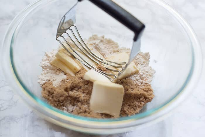 A pastry blender combines butter, flour, and brown sugar.