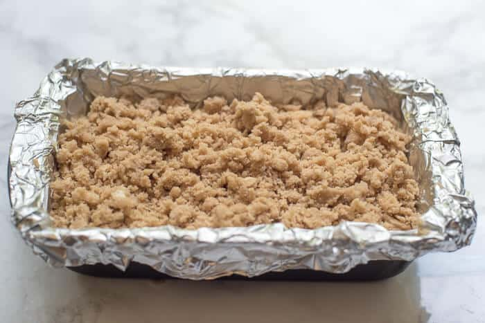 The crumb mixture on top of the cake batter in the loaf pan.
