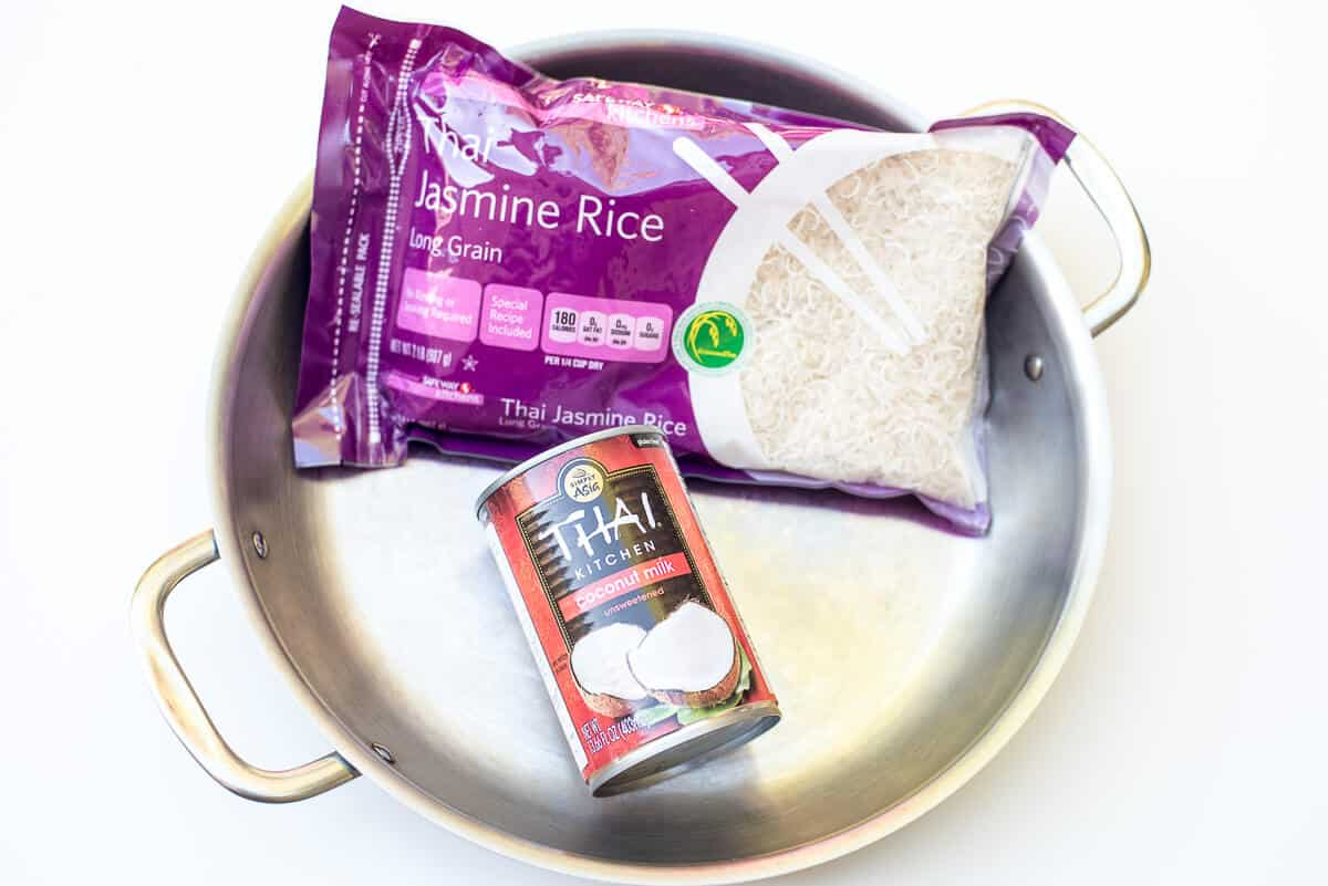A package of Jasmine Rice and a can of Thai Kitchen Coconut Milk in a stainless steel skillet.