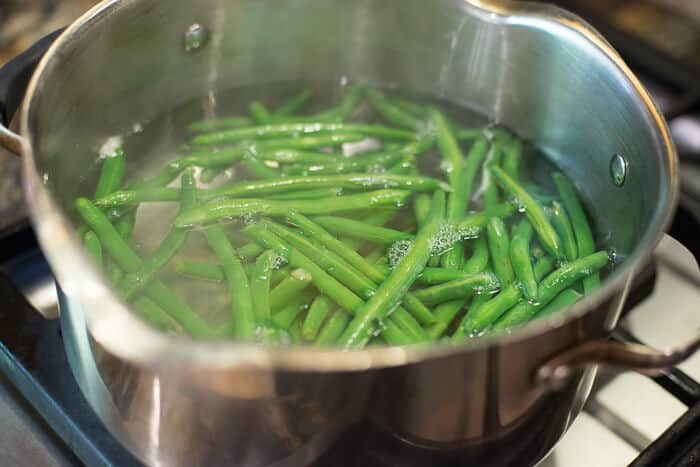 Green beans cooking in a pot of water on the stove.