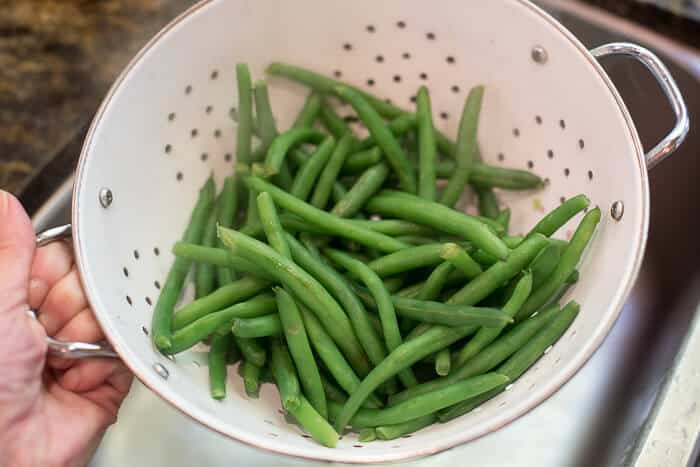 Green beans draining in a white colander.