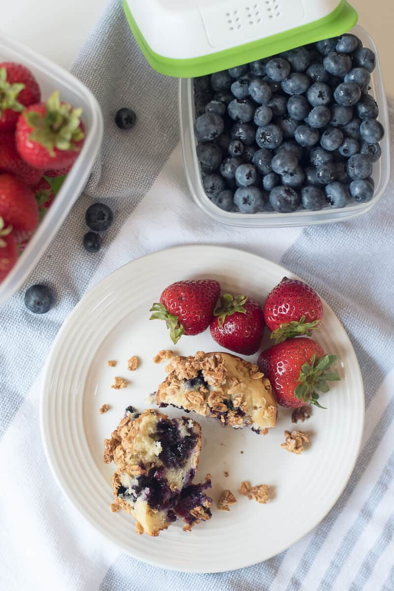 A muffin is broken in half on a white plate with Rubbermaid containers filled with fresh berries behind it.
