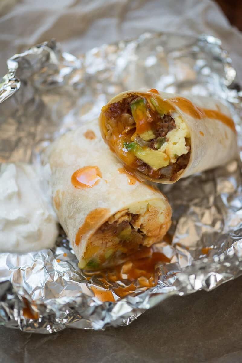A close up of a Corned Beef Hash Breakfast Burrito sliced in half on top of foil.
