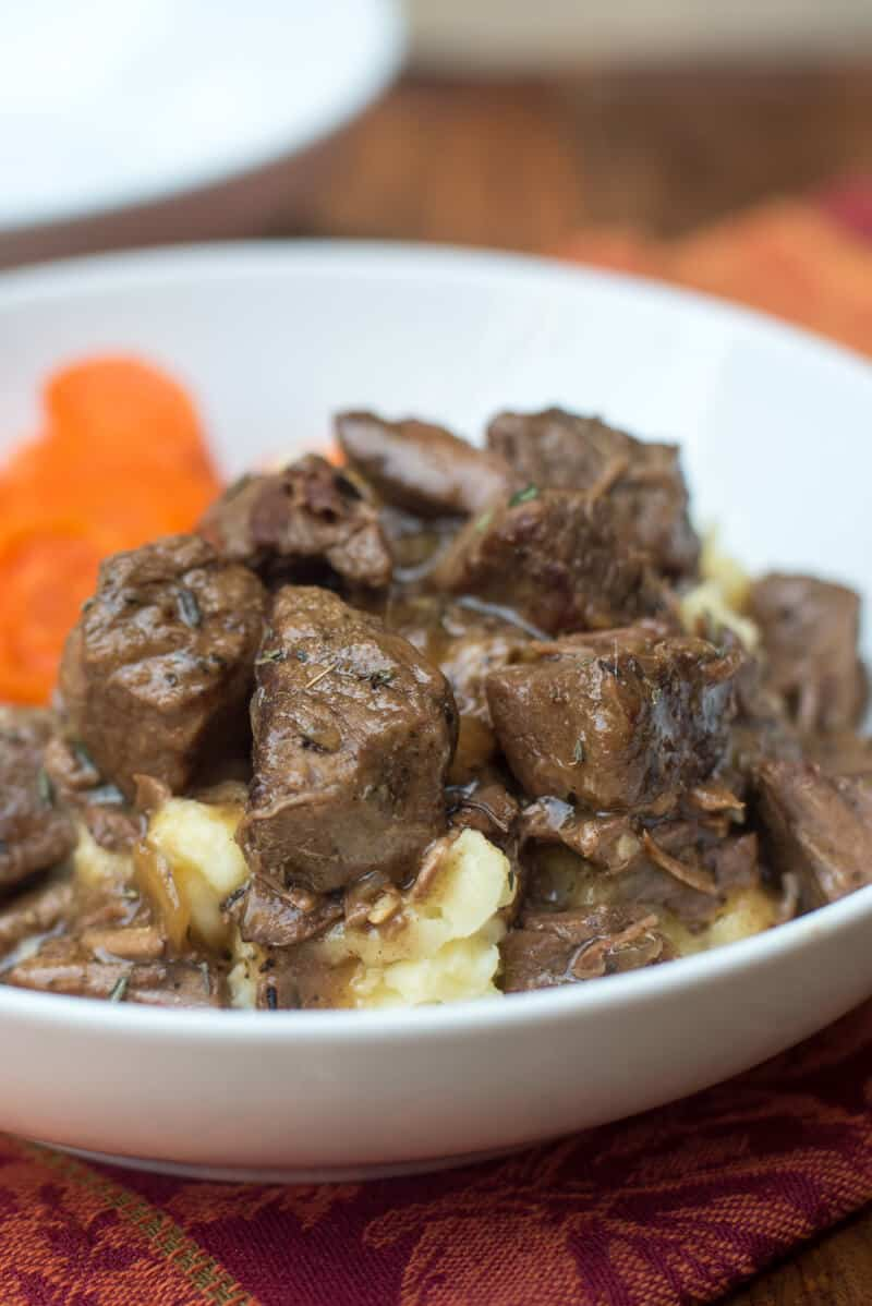 The beef tips with gravy spooned over a mound of mashed potatoes in a white serving bow.