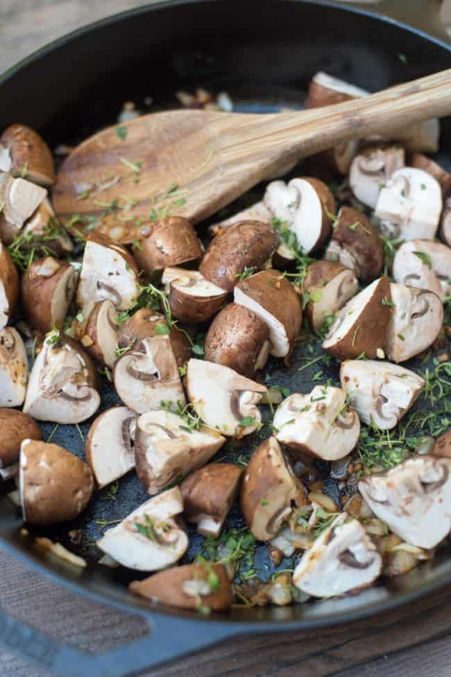Mushrooms and fresh thyme in a cast iron skillet.