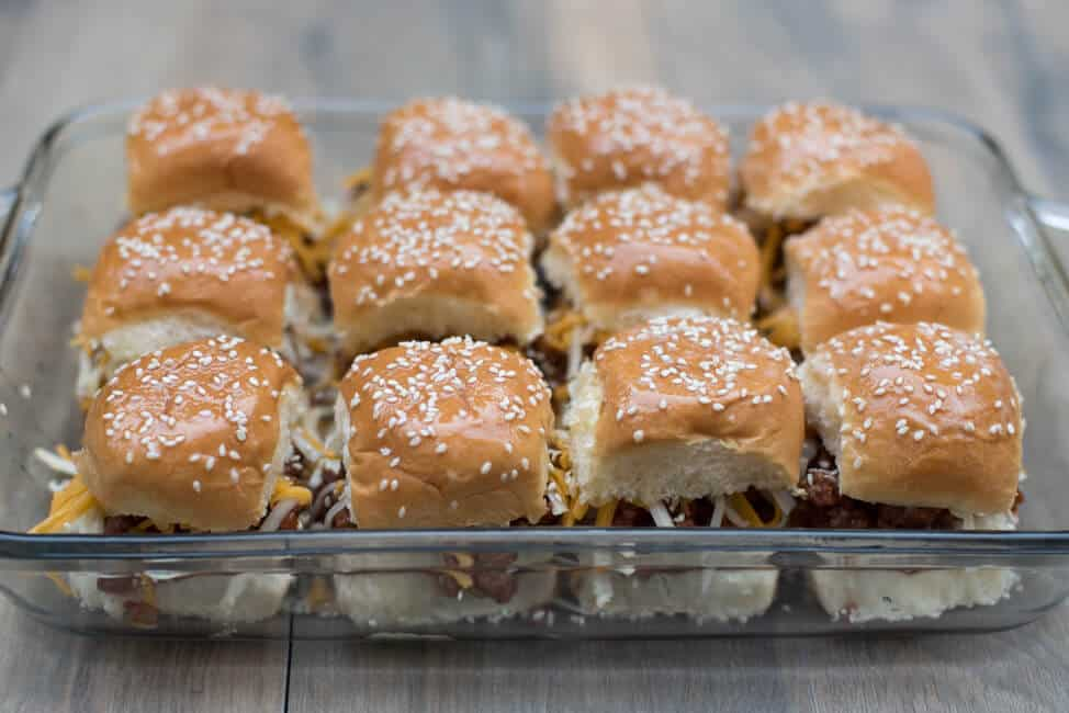 The top half of the buns is placed on top, brushed with melted butter and sprinkled with sesame seeds.