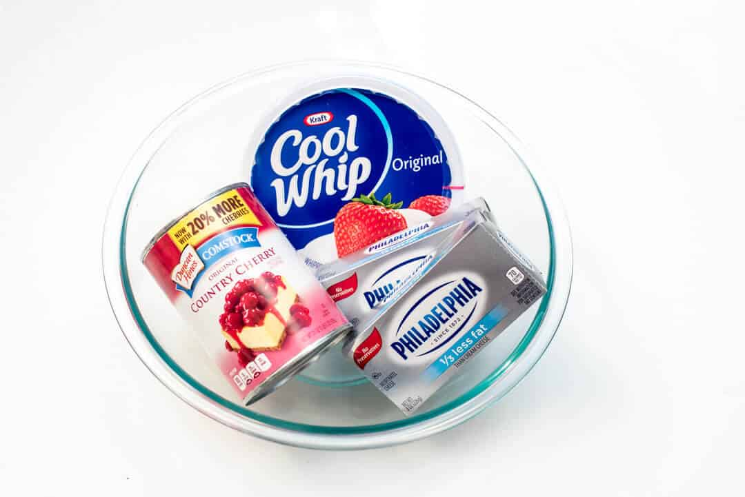 Comstock Country Cherry Pie Filling, Cool Whip, and Philadelphia Cream Cheese in a glass bowl.