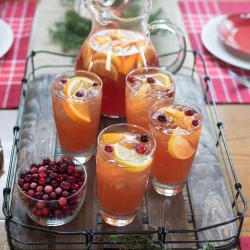 A table topped with festive table settings and a tray of iced tea.