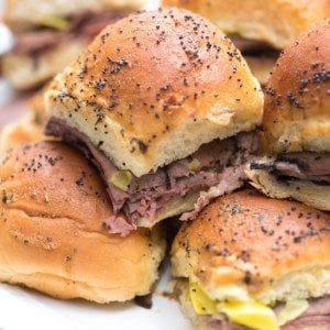 A close up of Italian Roast Beef Sliders stacked on a white plate.