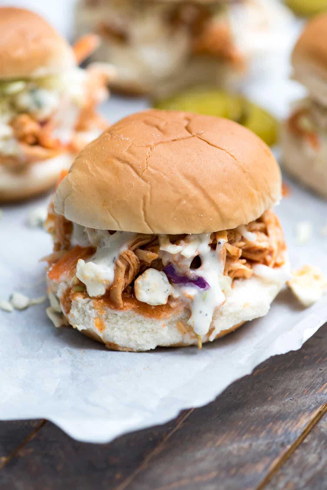 Slow Cooker BBQ Buffalo Chicken Sliders topped with crunchy coleslaw, a drizzle of Ranch dressing and crumbled blue cheese. Perfect for your game day menu!