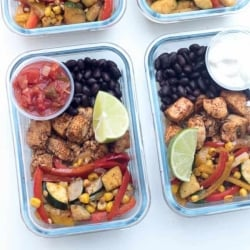 Glass meal prep containers filled with chicken, veggies, and black beans.