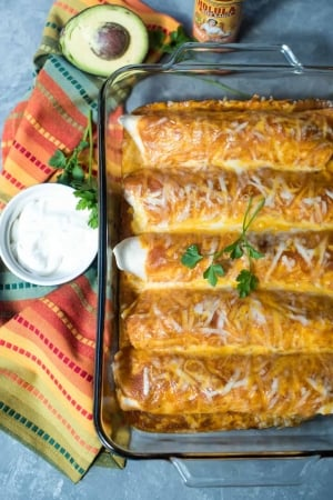 Enchiladas in a baking dish next to a small bowl of sour cream.