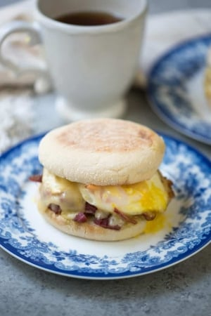 A breakfast sandwich on an English muffin on a blue and white plate.