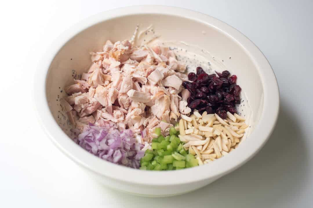 Chopped cooked chicken, dried cranberries, slivered almonds, chopped celery and red onion in the bowl with the poppy seed dressing.