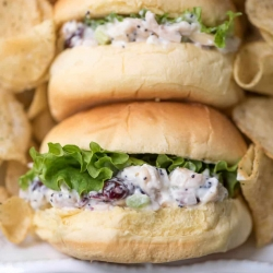 A close up of small buns filled with chicken salad and lettuce.