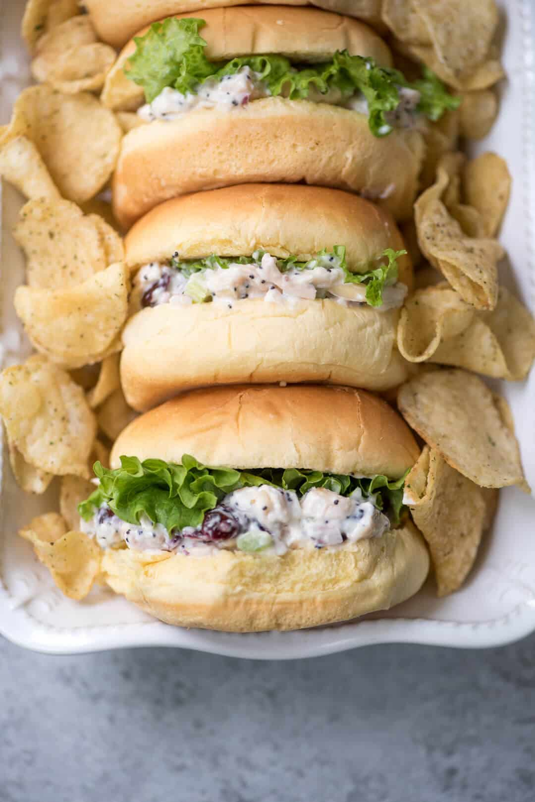 Cranberry Almond Poppy Seed Chicken Salad on potato buns with green leaf lettuce in a white serving dish with potato chips.
