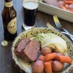 Slices of corned beef, carrots, and cabbage in a bowl with a bottle of Guinness.