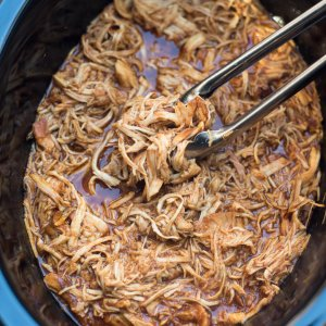 Metal tongs lifting shredded BBQ chicken from a slow cooker.