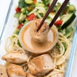 Chopsticks dipping a piece of chicken into peanut sauce.