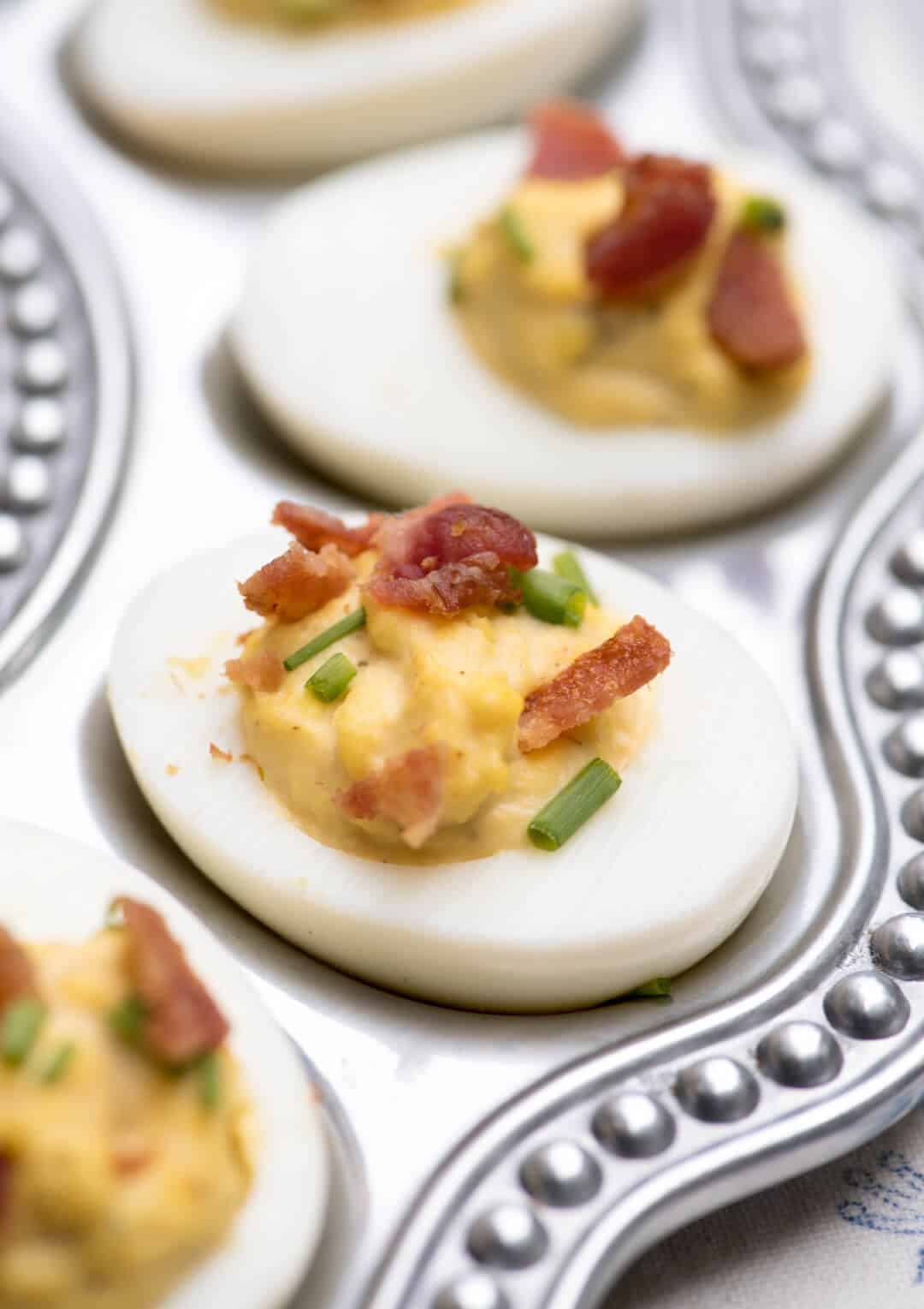 A close up shot of a Bacon Ranch Deviled Egg topped with chives and bacon.